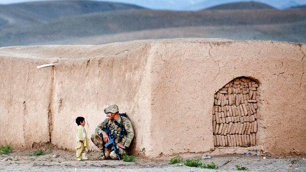 United States soldier chatting with Afghan boy in Afghanistan, 2012