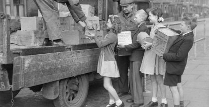 Children loading tins of biscuits for civilians in liberated Europe, 1945